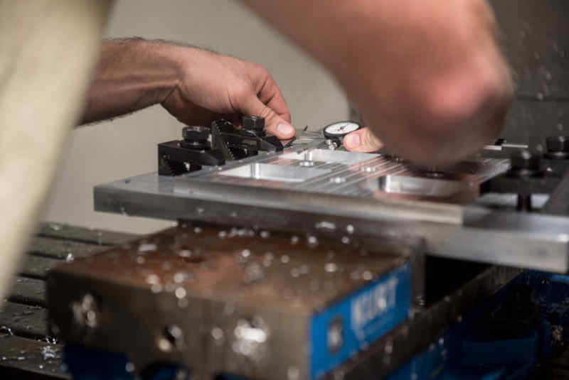 A CNC technician, measures and drill holes on an aluminum plate at Dover Air Force Base. The machinist is using the vertical mill CNC to engineer an aluminum plate for a helicopter.