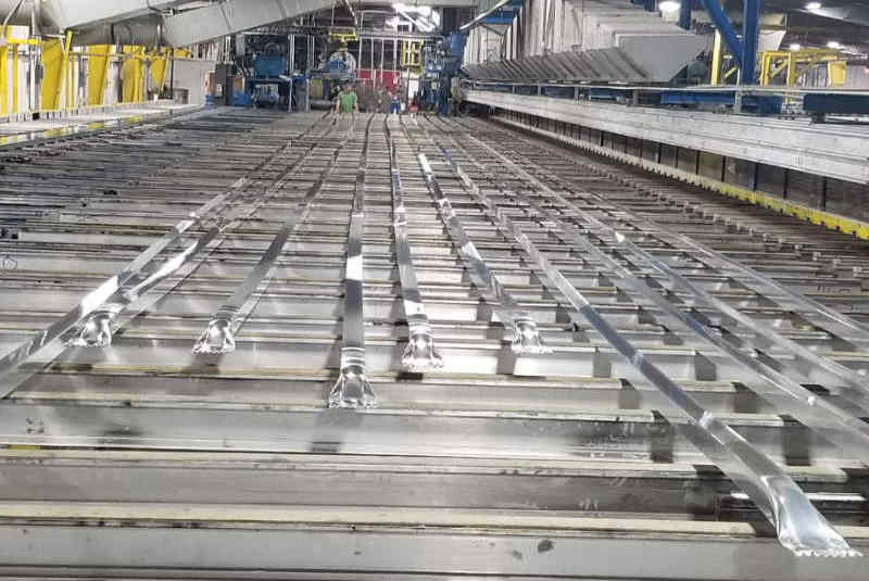 Custom aluminum extrusions lying in the cooling zone on the automated walkover table.